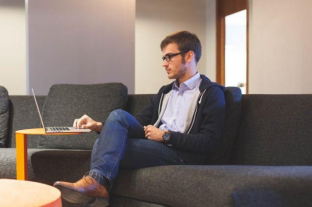 un jeun homme souscrit un prêt sur son ordinateur